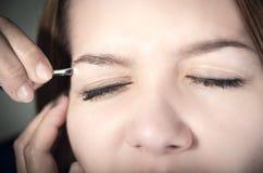 Beautiful young teen girl getting eyebrow plucked Stock Image