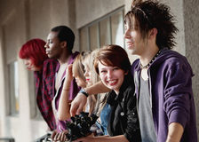 Beautiful young teen girl smiles. Young attractive teen punk looks towards the camera while her group of friends look away Stock Image