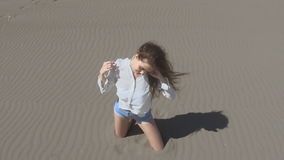 Beautiful young teen woman with blowing hair posing at camera, brunette on beach enjoying life, slow motion. Summertime stock footage