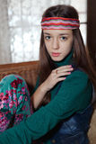 Beautiful young teenage girl hippie posing in room. Beautiful young teenage girl hippie sitting on wicker sofa and looking at the camera Royalty Free Stock Image