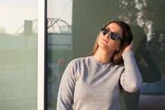 Beautiful young teenage smiling girl posing in front of the glass window royalty free stock photography