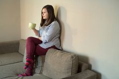 Beautiful young teenager girl at home setting on sofa. Drinking a drink from mug Stock Images