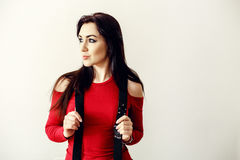 A beautiful young teenager girl in a red sweater and black suspender Royalty Free Stock Photos