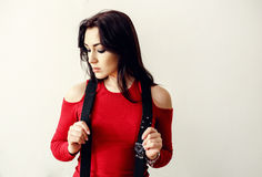 A beautiful young teenager girl in a red sweater and black suspender Royalty Free Stock Image