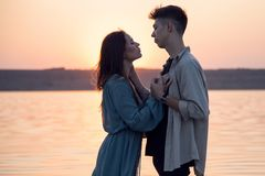 Beautiful young tender couple on the background of the sun. royalty free stock photo