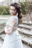 Beautiful young tender gay girl with beautiful wedding hairstyle with a snow-white smile in light dress is walking in spring Royalty Free Stock Photos