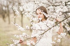 Beautiful young tender girl in blossom garden on a spring day, flower petals falling from the tree, closed her eyes and holding a royalty free stock photography