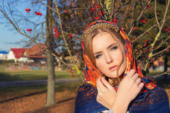 Beautiful young tender graceful girl in colored scarf on her head with a beautiful gold band with a gentle makeup stands Royalty Free Stock Photos