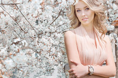 Beautiful young tender sweet girl flying in a light dress walking in a lush cherry orchard Royalty Free Stock Images