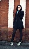 Beautiful young thoughtful girl near brick wall Stock Photo