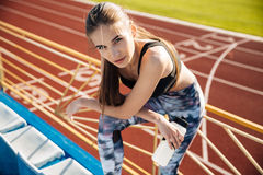 Beautiful young tired fitness girl resting after workout Royalty Free Stock Image