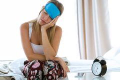 Beautiful young tired woman sitting on bed with sleep mask trying to wake up in bedroom at home. Shot of beautiful young tired woman sitting on bed with sleep royalty free stock photos