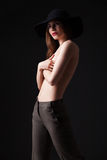 Beautiful young topless model in hat. Portrait of attractive young girl in black hat covering naked breast while looking away.Studio shot Royalty Free Stock Images