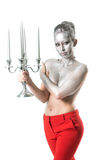 Beautiful young topless woman with evening hairstyle and upper body part and hair painted with silver color wearing red trousers Royalty Free Stock Photo