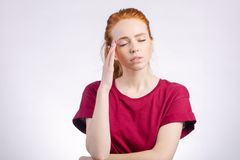 Beautiful young touching her temples feeling stress, on white background. Portrait of beautiful young redhead woman touching her temples feeling stress, on gray Royalty Free Stock Photos