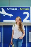 Beautiful young tourist girl with backpack and carry on luggage in international airport Royalty Free Stock Photos