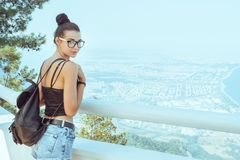 Beautiful young tourist girl with backpack near sea royalty free stock photography