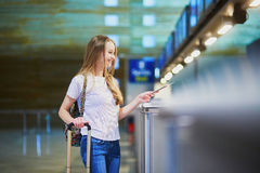 Beautiful young tourist girl in international airport at check-in counter Stock Photo