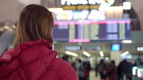 Beautiful young tourist girl in international airport or railway station, near flight information board stock video footage