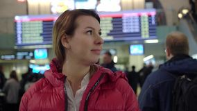 Beautiful young tourist girl in international airport or railway station, near flight information board stock footage