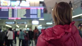 Beautiful young tourist girl in international airport or railway station, near flight information board stock video