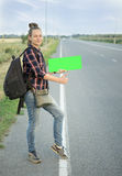 A beautiful young tourist girl, smiles, catches a hitchhiker. Concept: to travel the world, holidays, people, vacations. Royalty Free Stock Photos