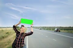 A beautiful young tourist girl, smiles, catches a hitchhiker. Concept: to travel the world, holidays, people, vacations. A beautiful young tourist girl, smiles Royalty Free Stock Photos
