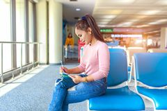 Beautiful young tourist sitting on a chair and writing record travel on notebook in international airport.  Stock Photography