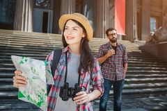 Beautiful young tourist stand in front and look forward. She smiles. Young woman holds map in one hand and binoculars in royalty free stock images