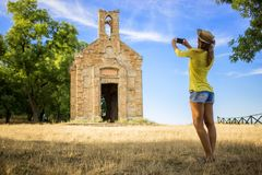 Beautiful young tourist taking a picture of a buidling. On a hill Stock Photos