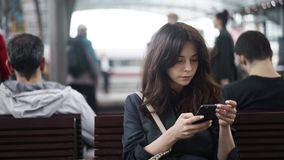 Beautiful young tourist texting on a bench in the Berlin Central Train Station. Beautiful young brunette tourist texting while sitting on a bench in the Berlin stock video