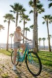 Joyful blonde woman riding bicycle in park having fun on summer afternoon royalty free stock photos