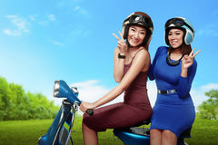 Beautiful young two asian woman with funny expression riding sco. Beautiful young two asian women with funny expression riding scooter together on the park Royalty Free Stock Photos