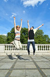 Beautiful young two girls in jump over the blue sky Royalty Free Stock Photography