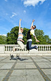 Beautiful young two girls in jump over the blue sky Royalty Free Stock Photos