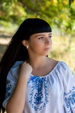 Beautiful young Ukrainian girl in national costume. Girl with beautiful appearance in the woods on the nature. Portrait. Stock Photos