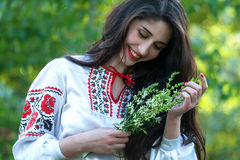 Beautiful young Ukrainian girl in national costume. Girl with beautiful appearance in the woods on the nature. Portrait/ Royalty Free Stock Image