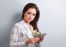 Beautiful young unhappy woman looking on dollars and thinking ho Stock Photos