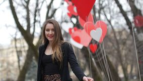 Beautiful young urban fashion girl plays with paper hearts decoration in the autumn park. Valentine's Day concept. Beautiful young urban fashion girl plays with stock video footage