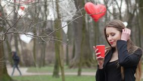 Beautiful young urban fashion woman in autumn park smiling and drinks cup of takeaway coffee. Happy blonde  girl. Outdoors stock footage