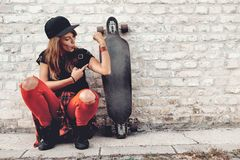 Cute urban girl with skateboard. Beautiful young urban girl with skateboard posing by brick wall Royalty Free Stock Images