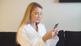Beautiful young uses smartphone to send photos after Spa treatments stock video