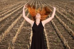 Beautiful young vital woman, in short black summer dress in nature on the field, raises her arms and throws her full long red royalty free stock images