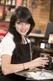Beautiful young waitress girl serving a drink Royalty Free Stock Photography