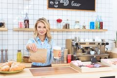 Beautiful young waitress holding coffee to go and take away food. In cafe stock image