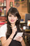 Beautiful young waitress taking an order Royalty Free Stock Photos