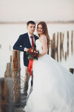 Beautiful young wedding couple, bride and groom posing near wooden poles on the background sea Royalty Free Stock Image