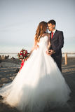 Beautiful young wedding couple, bride and groom posing near wooden poles on the background sea Royalty Free Stock Images