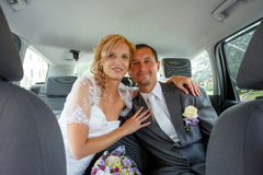 Beautiful young wedding couple in car Royalty Free Stock Images