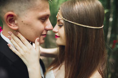 Beautiful young wedding couple is kissing and smiling in the park Stock Image